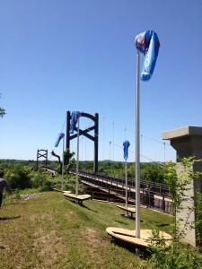 "Pier アーティスト: Derek Cote カンバーランド川を望むスロープに4.5mの吹き流しを伴ったベンチを4台設置。吹き流しには、川とコミュニティの人々を象徴する4つの言葉""Respect, Strength, Spirit, Depth""がプリントされている。"
